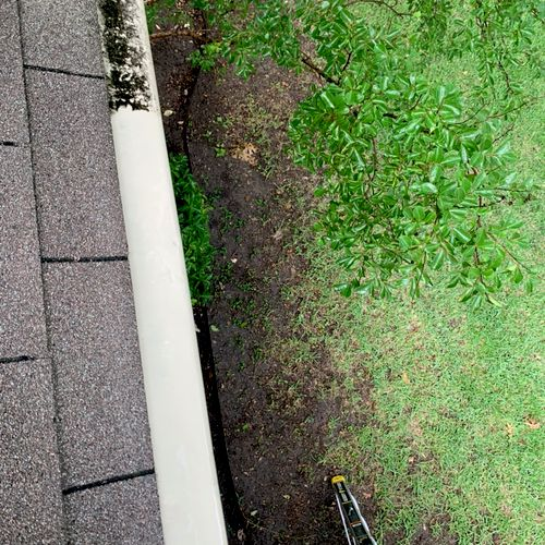 Side by side comparison of what the gutters looked like before cleaning and power washing them and what they look like after.
