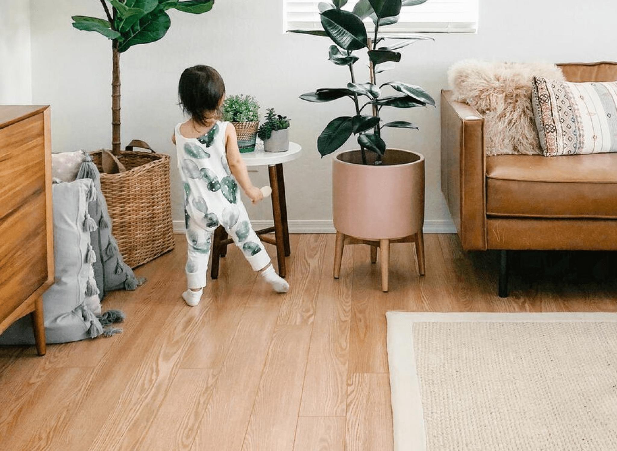 child walking on hardwood laminate flooring in living room