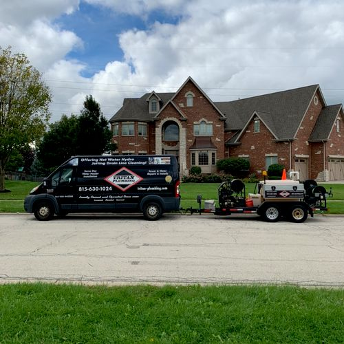 Tritan Plumbing team at a home clean a sewer line with the Hydro Jetter.