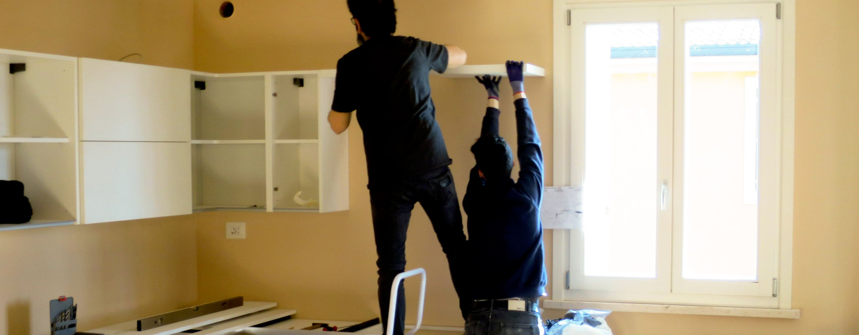 men adding shelves and cabinets to kitchen