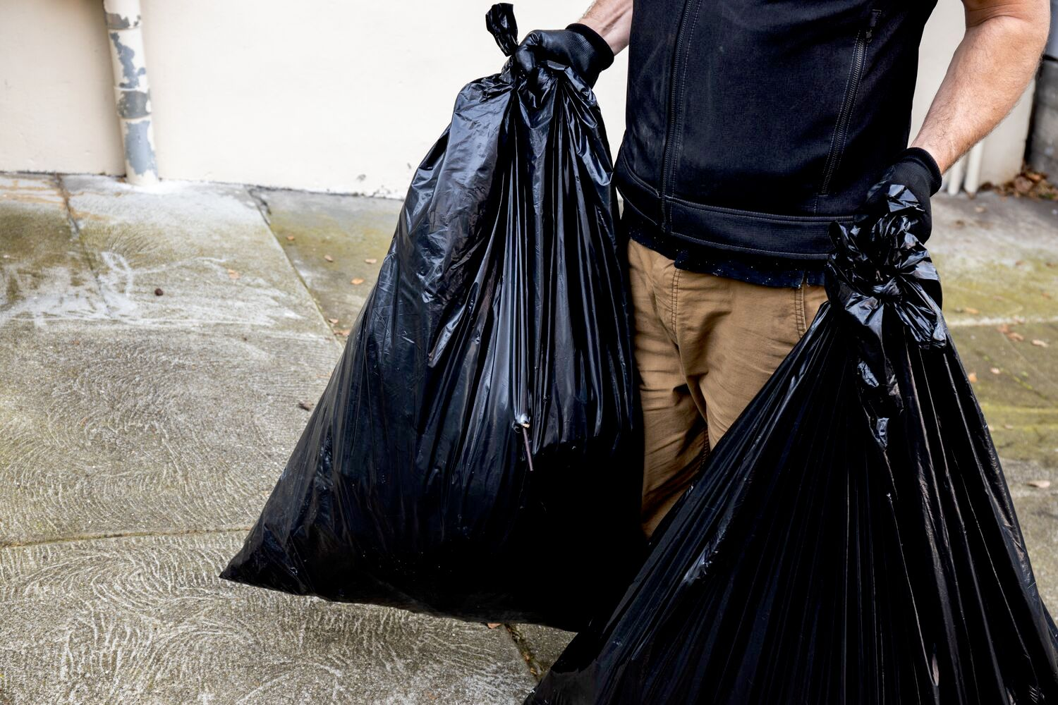 man carrying two trash bags