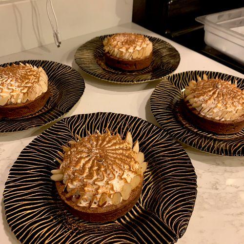 Triple chocolate tart Almond dark chocolate crust, Ruby chocolate ganache, marshmallow fluff, and cacao nib dust