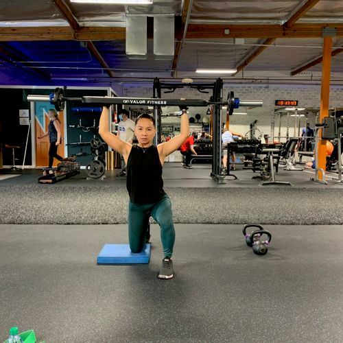 Kathleen doing the first exercise in a superset. By doing the military press on one knee she is also working her core stabilizer muscles.