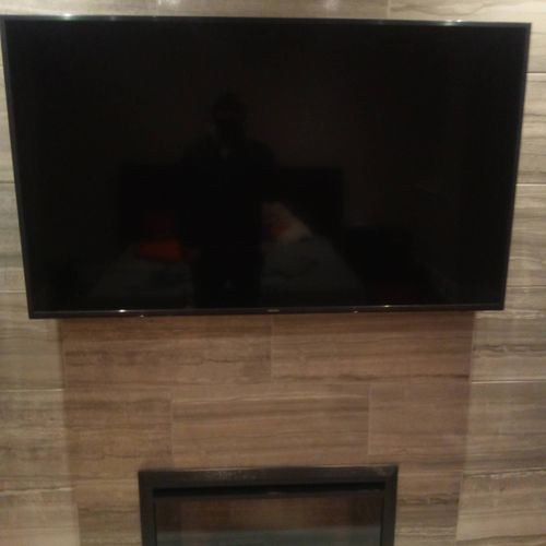 this TV was hung on a marble wall above a fireplace
