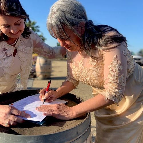 Mother of the bride & mother the groom signing the wedding license at a Livermore Winery