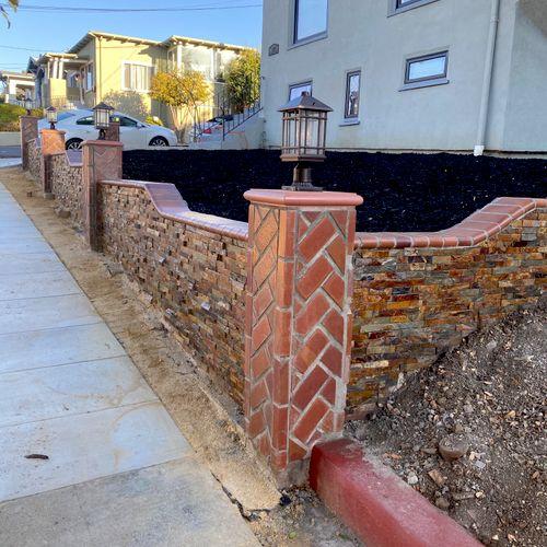 Retaining wall veneered with bricks and stones