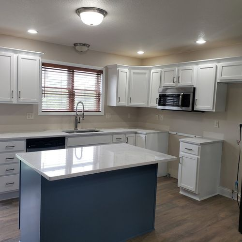 """We refinished Jenna in Ames' cabinets in """"Extra White"""" and her island in """"Smokey Blue"""". We also installed new cabinet handles and drawer pulls."""
