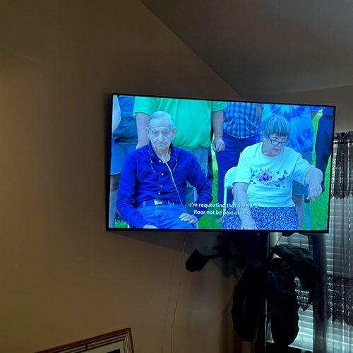 """70"""" Roku TV mounted on a full motion swivel mount. Affixed to the back of the TV is a Wii game console."""