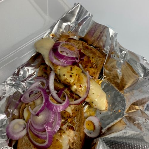 Grilled marinated chicken breast sandwich with provolone cheese and red onions on top of wheat toast