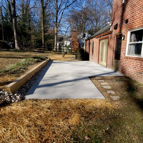 Concrete Patio with Tomber Wall and French drain to solve a water problem.